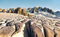 Crevasses and seracs of Explorer Glacier on top of Fox Glacier during summer sunset with Mt. Tasman dominating skyline, Westland Tai Poutini National Park, West Coast, UNESCO World Heritage Area, New Zealand, NZ