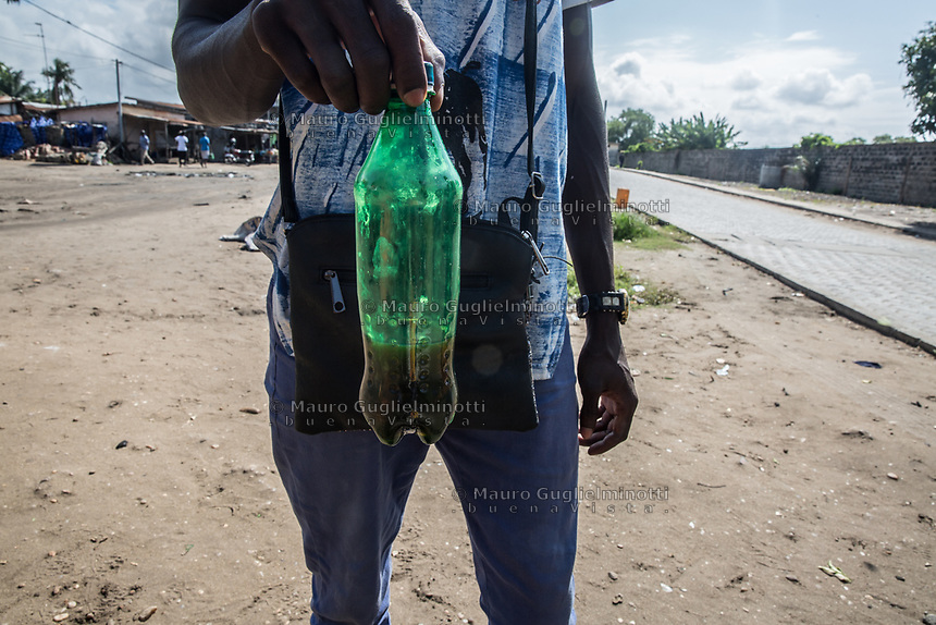Vendita di benzina di contrabbando - Smiggling Oil shop Traffico illegale benzina dalla Nigeria al Benin. un uomo mostra una bottiglia di benzina
