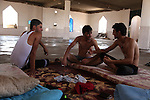 DOMIZ, IRAQ: Three Syrian refugees chat inside a mosque in the Domiz refugee camp where they are living...Over 7,000 Syrian Kurds have fled the violence in Syria and are living in the Domiz refugee camp in the semi-autonomous region of Iraqi Kurdistan...Photo by Ari Jalal/Metrography