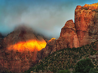 Sunrise peaking through storm clouds.with fall color Towers of the Virgin. Zion National Park, Uta