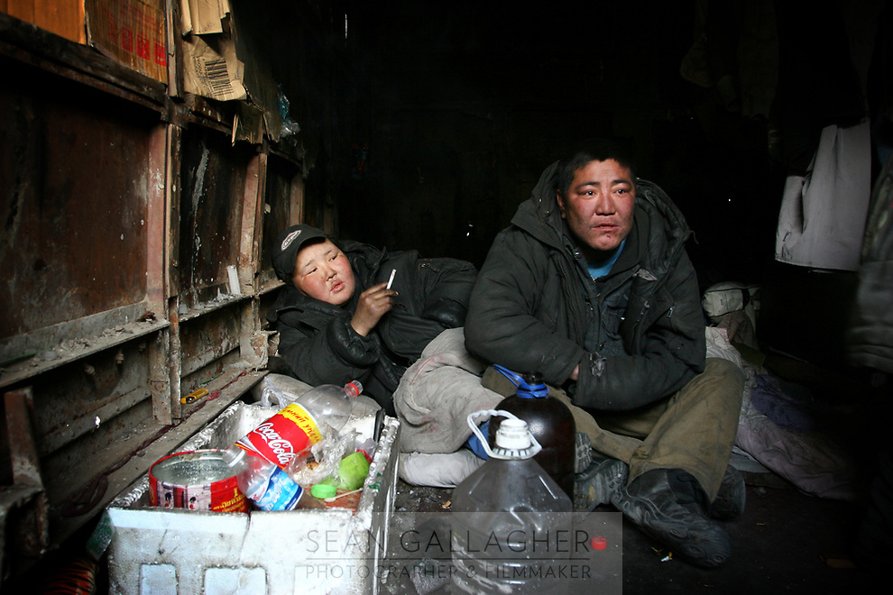 MONGOLIA. Ulaan Baatar. Otguntugs,28, (right) and Ounsuren (left), 36, in their garage-home. <br /> As the global financial crisis grips Asia, Mongolia is feeling the implications first hand as the country suffers from rising inflation pushing the price of food and fuel ever upwards. For the country's homeless, who live in sewers and abandoned garages in the capital and already face extreme discrimination and are denied access to basic health and social care, their lives are hanging in the balance. 2008