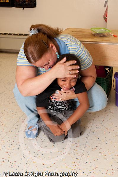 Education preschool 3 year olds separation first days of school female teacher comforting sad boy