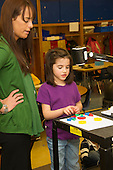 MR / Schenectady, NY. Zoller Elementary School (urban public school). Kindergarten inclusion classroom. Teacher listens as student (girl, 5) speaks to class as she works with shape blocks during math lesson. Digital visual presenter magnifies and projects the shape blocks onto digital whiteboard screen so the rest of the class can follow along. MR: War15, Coh2. ID: AM-gKw. © Ellen B. Senisi.