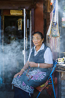 Lady in Paro sits outside her home holding buddhist meditation beads surrounded by incense smoke. The people in Bhutan are extremely friendly and she was happy to chat and have her photograph taken.