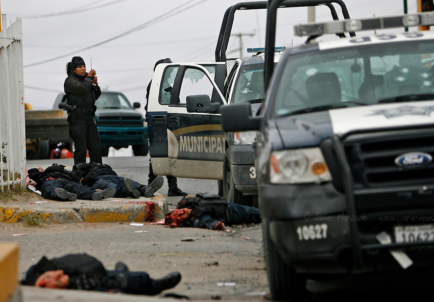 A federal police officer calls for help as they check for survivors after arriving at the scene where a convoy of federal and municipal police were ambushed on Friday, April 23, 2010. The toll for this day left  six federal police officers, one female municipal police and one civilian dead as they lay outside a gasoline station on the corner of Santiago Troncoso and Durango Ave. in Ciudad Juarez. Another woman who was tending to her local business was wounded and transferred to a nearby hospital. According to witnesses, three vehicles closed in on the officers with high caliber weapons and opened fire on them around 12:30 pm. ..©Javier Manzano