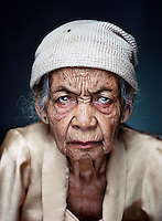 "Wainem (born 1925) was one of tens of thousands of 'comfort women' forced into prostitution by the Japanese military during World War II..Wainem was taken from home and forced into prostitution, first in Solo for a year and then for two years in Yogyakarta. During the day in a warehouse, she had to weave mats with other women and cook her own food. Sometimes she was raped right then and there, but most of the time was taken by soldiers to their rooms in the barracks compound. ""An Indonesian doctor tested us every week for pregnancy while a Japanese doctor observed. I never became pregnant then."" After the war, with a group of women, she walked some 60 miles to get home. ""Our people chased off the Japanese with bamboo spears. They confiscated everything: our rice, our money, our gold. When at night the air-raid sirens sounded and we had to hide, the Japanese entered our homes and emptied them."" She would rather not be reminded of what happened in that warehouse. ""It's so long ago. My son, who wasn't born then, has grandchildren of his own now.""."