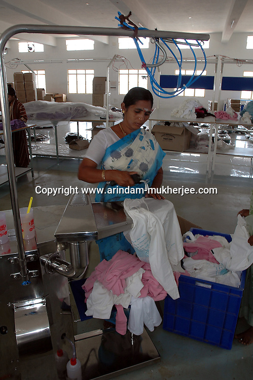 An Indian lady working with a sophisticated stain removing machine at Srinidhi garment stitching factory in Tirupur, Tamilnadu. After lifting of quota system in textile export on 1st january 2005. Tirupur has become the biggest foreign currency earning town of India.