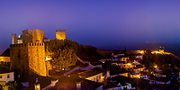 Panorama of the lit-up city wall and houses of the beautiful, old village of Obidos, during a colorful morning twilight, in Portugal Europe