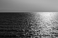 Shining, rippling water in black and white with faint mountain outline on the horizon.  Shining sun reflection on right with copy space on left and on top.