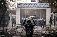 Pictured: Migrants react to tear gas deployed by Greek riot police Greek riot police by the Turkish side of the border in Andrianoupolis. Sunday 01 March 2020<br /> Re: Clashes between migrants and riot police at the Greek-Turkish border of Kastanies near Evros, Greece