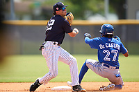 FCL Yankees second baseman Jose Colmenares (12) throws to first base as Rikelin De Castro (27) slides in during a game against the FCL Blue Jays on June 29, 2021 at the Yankees Minor League Complex in Tampa, Florida.  (Mike Janes/Four Seam Images)