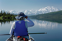 A woman pauses and looks through binoculars from a canoe in Wonder Lake. A clear view of Mt. McKinley is a special day in Denali National Park, Alaska.