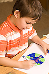 Education elementary Kindergarten art activity drawing with markers boy drawing globe earth vertical