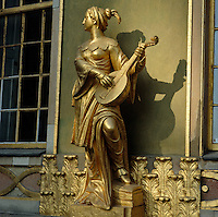 A gilded female figure playing the lute stands between two windows on the exterior of the Chinese Tea Pavilion in the Sanssouci Park, Potsdam