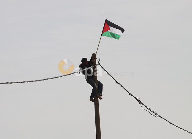 """A Palestinian protester climbs on an electricity pole to hang a national flag during a demonstration on February 24, 2010 on the outskirts of Gaza City against the military zone Israel created on Palestinian land, east of the city, as a buffer between its border areas and the Hamas-run Gaza Strip. Israel created the """"security zone"""" during its 22-day military offensive into Gaza between late December 2008 and January 2009. Some 1,400 Palestinians and 13 Israelis were killed during the conflict, which followed unrelenting rocket-fire into Israel from the Palestinian enclave. Photo by Mohammed Othman"""