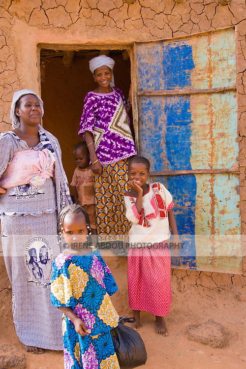 """A friendly group of women and children greet me as I walk through the town of Torodi in southwestern Niger. They stand in front of their handmade mud-brick house. Each year, an extra coating of mud is smeared on the outside walls to keep the rain from washing the bricks away and the house from falling. The roof of the house is a thin sheet of aluminum held up by cylindrical wood beams collected in the """"bush."""""""