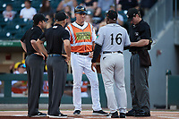 Charlotte Traffic Cones manager Wes Helms (18) meets with Norfolk Tides fundamentals coach Ramon Sambo (16) and umpires Jonathan Parra, Billy Cunha, and Alex Tosi prior to their Triple-A East game at Truist Field on August 20, 2021 in Charlotte, North Carolina. (Brian Westerholt/Four Seam Images)