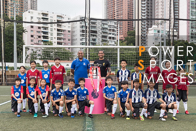 Mark Sutcliffe (L), Phil Babb (R) and Hong Kong children pose for a group photo with the Premier League Asia Trophy in front of the Hong Kong skyline for the launch of the Premier League Asia Trophy 2017 at the Hong Kong Football Club on 01 June 2017 in Hong Kong, China. Photo by Chris Wong / Power Sport Images