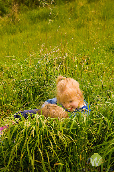 Margaret Rose Wellings playing with friend in grass.