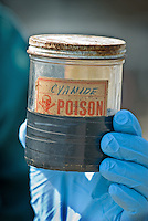 A hazardous waste worker holds an aging container labeled as cyanide after it was dropped off at a hazardous waste disposal site in Westerville, Ohio. Homeowners were able to remove any hazardous waste from their homes to be properly recycled or disposed of instead of placing in their trash or pouring down the drain.<br />