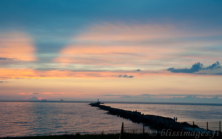 A couple leaves breakwater at Sunset