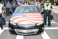 People drive a Chevrolet sedan with an American flag hood in the Straight Pride Parade in Boston, Massachusetts, on Sat., August 31, 2019.