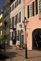 Charleston, SC, South Carolina, A man walks his dog along Rainbow Row, a collection of colorful historical houses, along East Bay Street in Charleston in the spring.