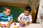 Education preschoool children ages 3-5 art activity two boys playing with play dough horizontal one boy looking at what the other is doing