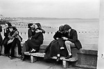 Teenage couples on holiday Easter Sunday Bridlington Yorkshire, 1972, The wooden door on the right of this photograph I think was acting as a wind break.