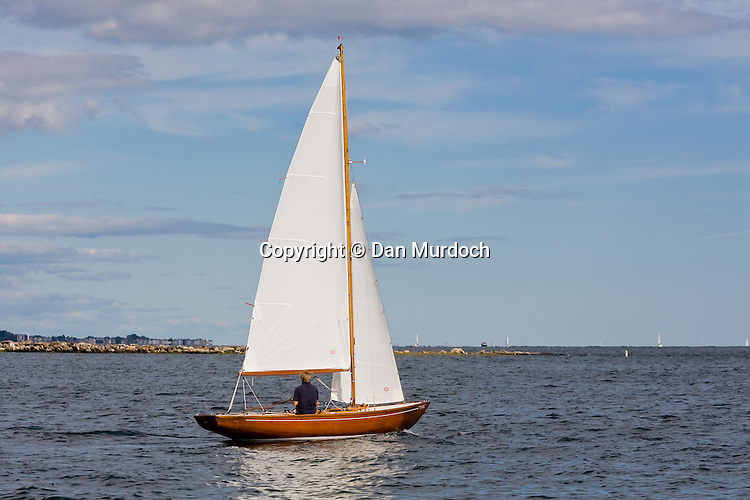 Small classic wood sloop sailing