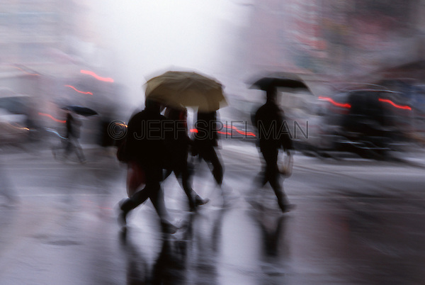 AVAILABLE FOR COMMERCIAL AND EDITORIAL LICENSING EXCLUSIVELY FROM GETTY IMAGES.  Please go to www.gettyimages.com and search for image # 200184790-001<br /> <br /> People Crossing East Broadway in the Rain, Chinatown, New York City, New York State, USA