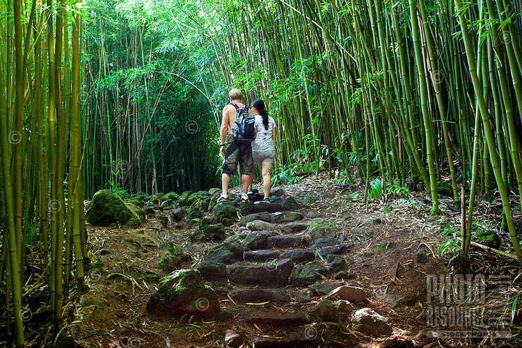 A couple walks through a bamboo forest along the Pipiwai hiking trail in Haleakala National Park, Maui.