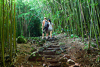 A couple walks through a bamboo forest along the Pipiwai hiking trail in Haleakala National Park, Maui.