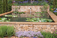 Herbs including rosemary, thyme, lavander, with stone aboveground water garden and waterlilies