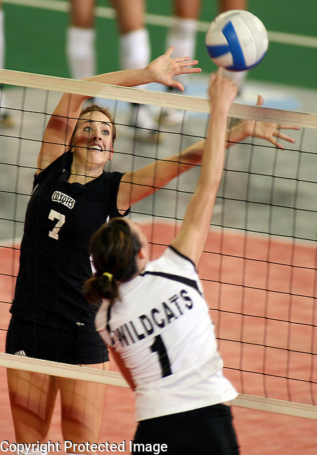 University of South Dakota's Kathleen Hruska (7) tries to block a kill attempt by Wayne State's Danielle Wessel (1) during the third game of their match Saturday night, Oct. 13, 2007 at the DakotaDome in Vermillion. (photo by Dave Eggen/Inertia)