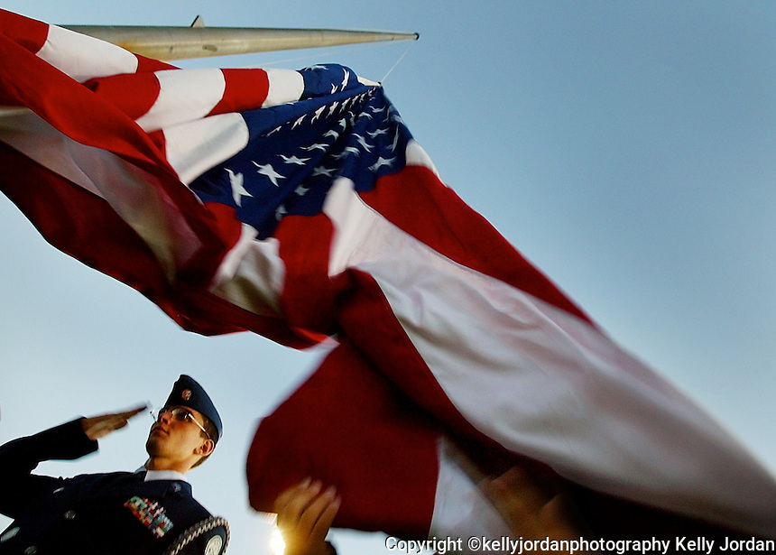 Pine Ridge High School Air Force Junior ROTC Cadet Captain Matt Berard, a junior, salutes as Cadet 1st Lt. Lined Agostini, a senior gently lets go of the American Flag as they raise it during playing of the National Anthem before the Pine Ridge High School football game against Mainland Friday night, October 24, 2003 in Deltona.(UCF/Kelly Jordan)..