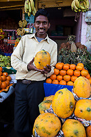 India, Dehradun.  Fruit and Vegetable Vendor Holding a Papaya in a Streetside Market.