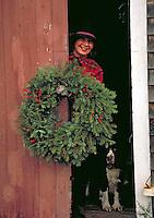 Woman placing Christmas wreath, holiday, tradition.