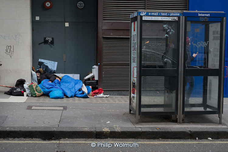 Elderly man and a woman sleeping in a doorway close to Oxford Street, central London.