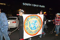 Occupy Orange County protestors march in front of a South Coast Plaza sign early in the morning (1:10am) on Black Friday. The protesters were tied together by rope, being led by a single protestor dressed in a suit (as a banker), symbolizing how the 1% lead the 99%.