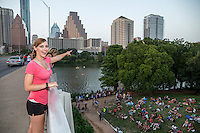 Fun attractive female tourist points with excitement on the Congress Ave. Bat Bridge, millions of bats take flight nightly at dusk in downtown Austin, Texas.
