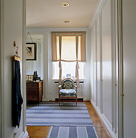 A carved Louis XVI chair upholstered in blue and white printed damask stands beneath the window of this dressing room