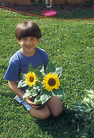 Boy sitting amiling with sun flowers in garden on lawn in backyard