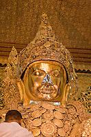 Myanmar, Burma.  Mandalay.  Mahamuni Buddhist Temple.  Face of the Mahamuni Buddha.  The Buddha is covered in gold leaf.  Only males are allowed to approach the Mahamuni Buddha.