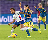 ORLANDO, FL - JANUARY 22: Crystal Dunn #19 of the USWNT is defended by Daniela Montoya #6 of Colombia during a game between Colombia and USWNT at Exploria stadium on January 22, 2021 in Orlando, Florida.