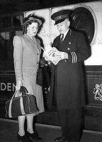 """Mr Donald White, """"The Man from Cook's"""" assists a woman traveller on the Golden Arrow train at Victoria station.<br /> April 1948"""