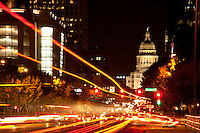 Congress Avenue traffic light trails with the Texas State Capitol serves as majestic backdrop