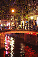Neon reflections in canal in red light district, Amsterdam. People and bike on the bridge