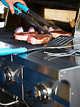 Closeup of a gas grill. A hand is seen placing pork chops and red onions on it with tongs.