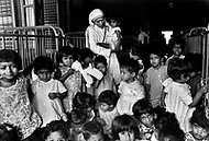 """Calcutta, India. April 04, 1975. Mother Teresa in her orphanage spending time with each of them. She takes long hours in the morning to talk and confront them. Mother Teresa (Agnes Gonxha Boyaxihu) the Roman Catholic, Albanian nun revered as India's """"Saint of the Slums,"""" was awarded the 1979 Nobel Peace Prize."""